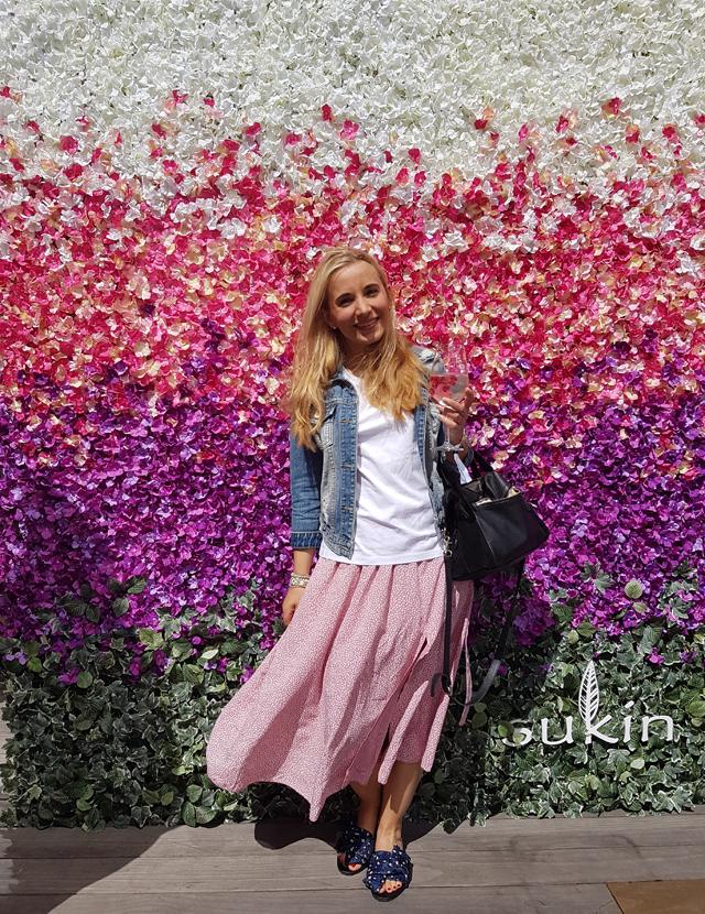 Marie vor einer Blumenwand
